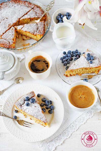 proste ciasto z owocami podane z borówkami i cukrem pudrem oraz kawą