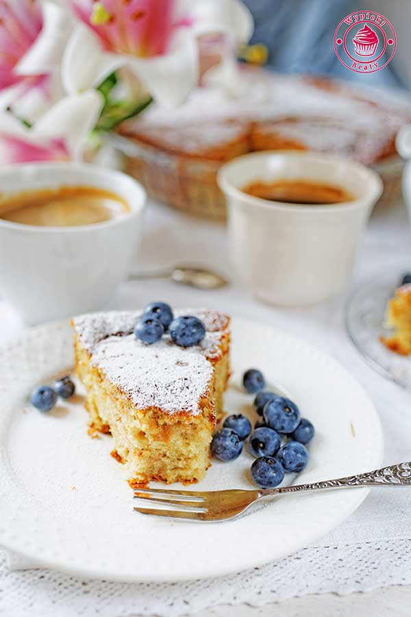 proste ciasto z tartymi jabłkami posypane cukrem pudrem podane z borówkami amerykańskimi